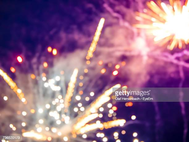 defocused image of fireworks display at night - firework display stock photos and pictures