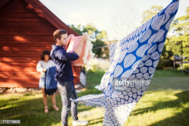 Defocused image of friends drying laundry at backyard