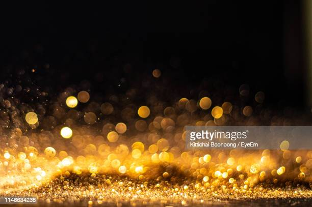 defocused image of glitter against black background - illuminated stock pictures, royalty-free photos & images