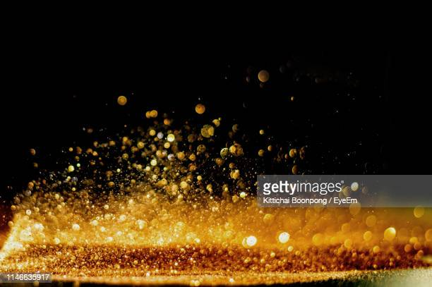 defocused image of glitter against black background - shiny stock pictures, royalty-free photos & images