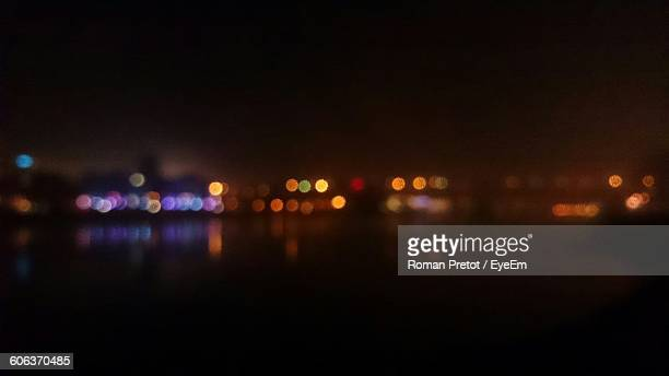 Defocused Image Of Illuminated Buildings With Reflection In River Against Sky