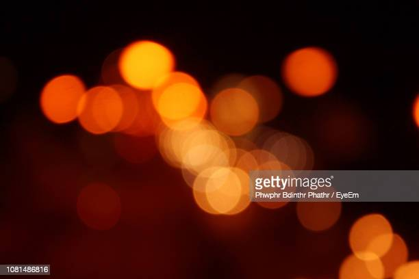 defocused image of illuminated christmas lights at night - blendenfleck stock-fotos und bilder