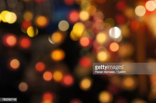 Defocused Image Of Illuminated Christmas Lights At Night