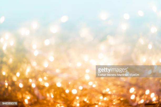 defocused image of illuminated christmas lights at night - gold background - fotografias e filmes do acervo
