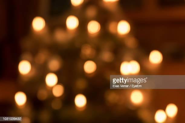 defocused image of illuminated christmas lights - licht stock-fotos und bilder