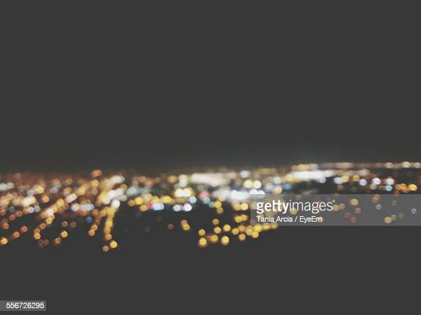 Defocused Image Of Illuminated City Against Clear Sky At Night
