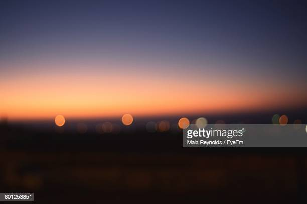 Defocused Image Of Illuminated City Against Sky