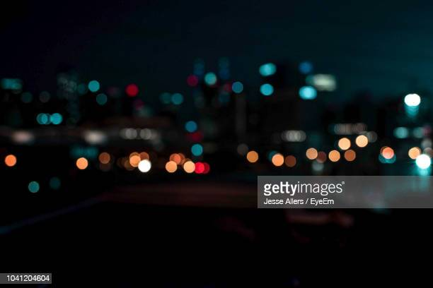 defocused image of illuminated city at night - blendenfleck stock-fotos und bilder