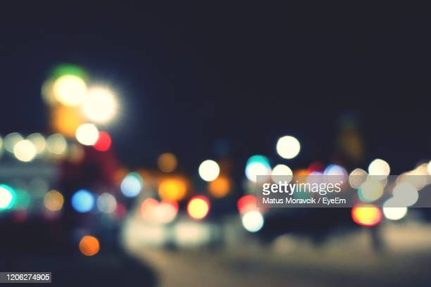 defocused image of illuminated city at night - urban road stock pictures, royalty-free photos & images