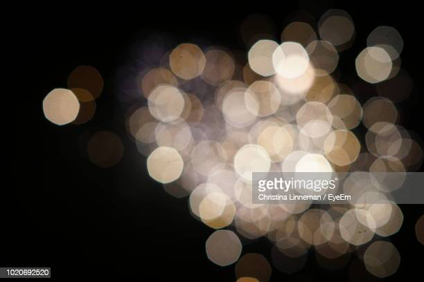 defocused image of illuminated lights against black background - blendenfleck stock-fotos und bilder