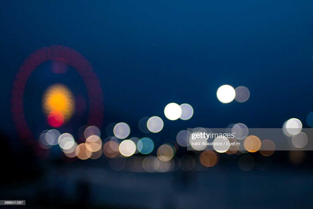 Defocused Image Of Illuminated Lights Against Sky At Dusk : Stock Photo