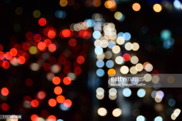 defocused image of illuminated lights at night - vehicle light stock pictures, royalty-free photos & images