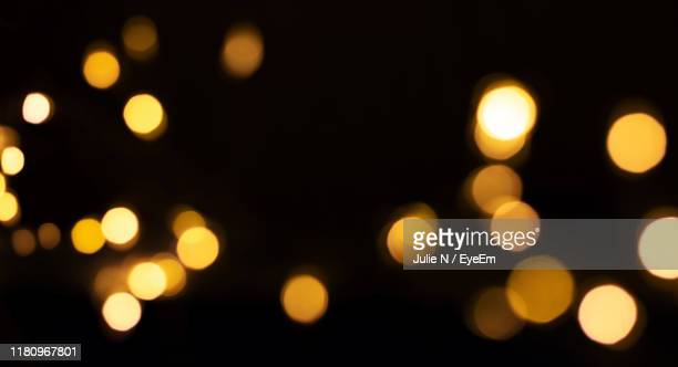 defocused image of illuminated lights at night - lens flare stock pictures, royalty-free photos & images