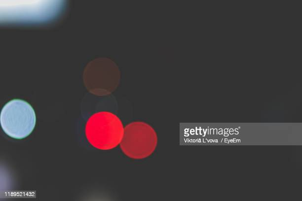 defocused image of illuminated lights at night - red light stock pictures, royalty-free photos & images