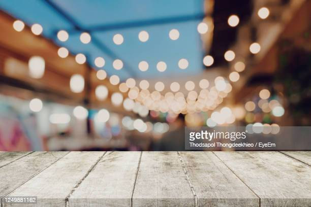 defocused image of illuminated lights at night - wood material stock pictures, royalty-free photos & images