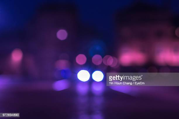 defocused image of illuminated lights at night - purple stock pictures, royalty-free photos & images