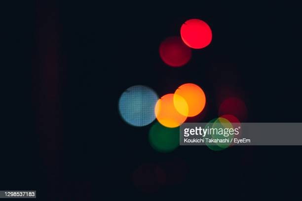 defocused image of illuminated lights on street at night - koukichi stock pictures, royalty-free photos & images
