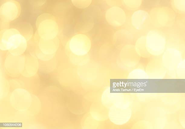defocused image of illuminated lights - gold background - fotografias e filmes do acervo