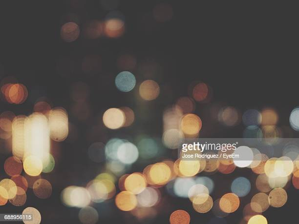 defocused image of illuminated street lights at night - riflesso sull'obiettivo foto e immagini stock