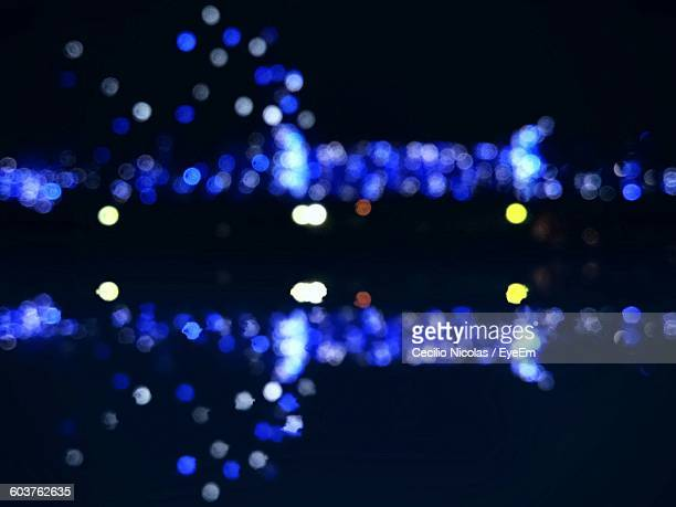 Defocused Image Of Lake By Illuminated Decorations At Night