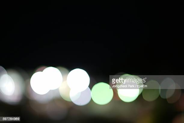Defocused Image Of Lights Against Clear Sky At Night