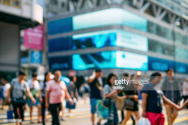 defocused image of pedestrians crossing the street in downtown hong kong against contemporary highrise city buildings - prosperity stock pictures, royalty-free photos & images