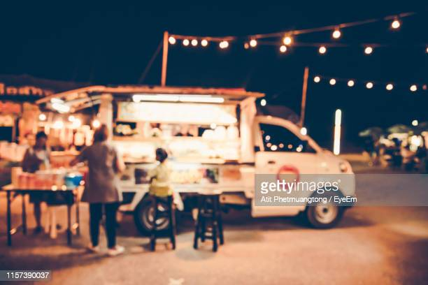 defocused image of people by food truck at night - food truck stock pictures, royalty-free photos & images