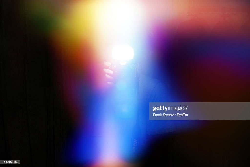 Defocused Image Of Person Photographing Amidst Colorful Lights : Stock-Foto