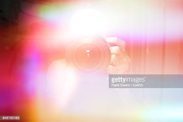 defocused image of person photographing amidst colorful lights - frank swertz stockfoto's en -beelden