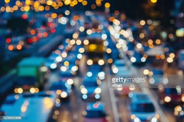 defocused image of rush hour traffic on busy highway in the evening - traffico foto e immagini stock