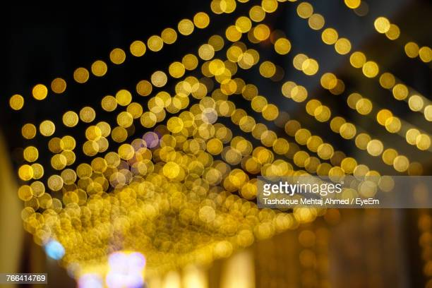 defocused image of string lights at night - diwali celebration stock photos and pictures