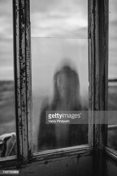 defocused image of teenage girl seen through window of old lookout tower - teen russia stock photos and pictures