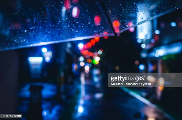 defocused image of wet street at night view from my umbrella - koukichi stock pictures, royalty-free photos & images