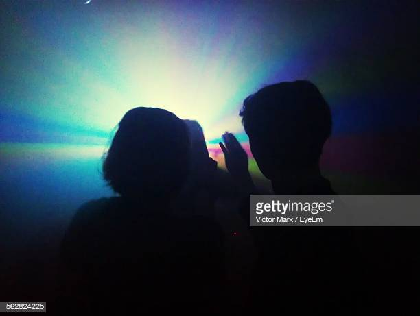 Defocused Image Of Young Women Dancing At Nightclub