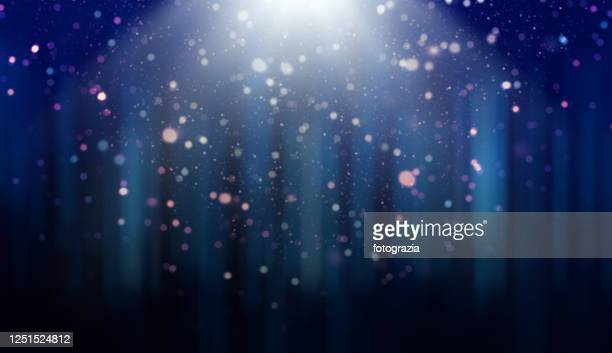 defocused lights, dust particles and light rays over gradient blue background - falling stock pictures, royalty-free photos & images