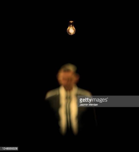 defocused mistery man in dark under light bulb - mistery foto e immagini stock