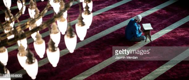 defocused muslim praying inside mosque on carpet - koran stock pictures, royalty-free photos & images