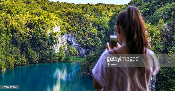 Defocused Of Girl Taking A Picture Of Nature With Smartphone