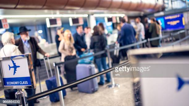 Defocused photo of people boarding to economy class at an airport