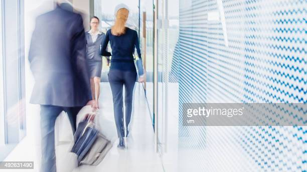 Defocused shot of business people walking in modern office corridor