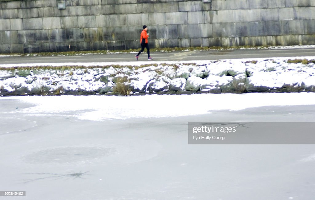 Defocused single female jogger running along riverside in snow : Stock Photo