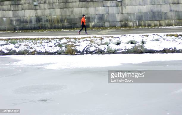 defocused single female jogger running along riverside in snow - lyn holly coorg stock pictures, royalty-free photos & images