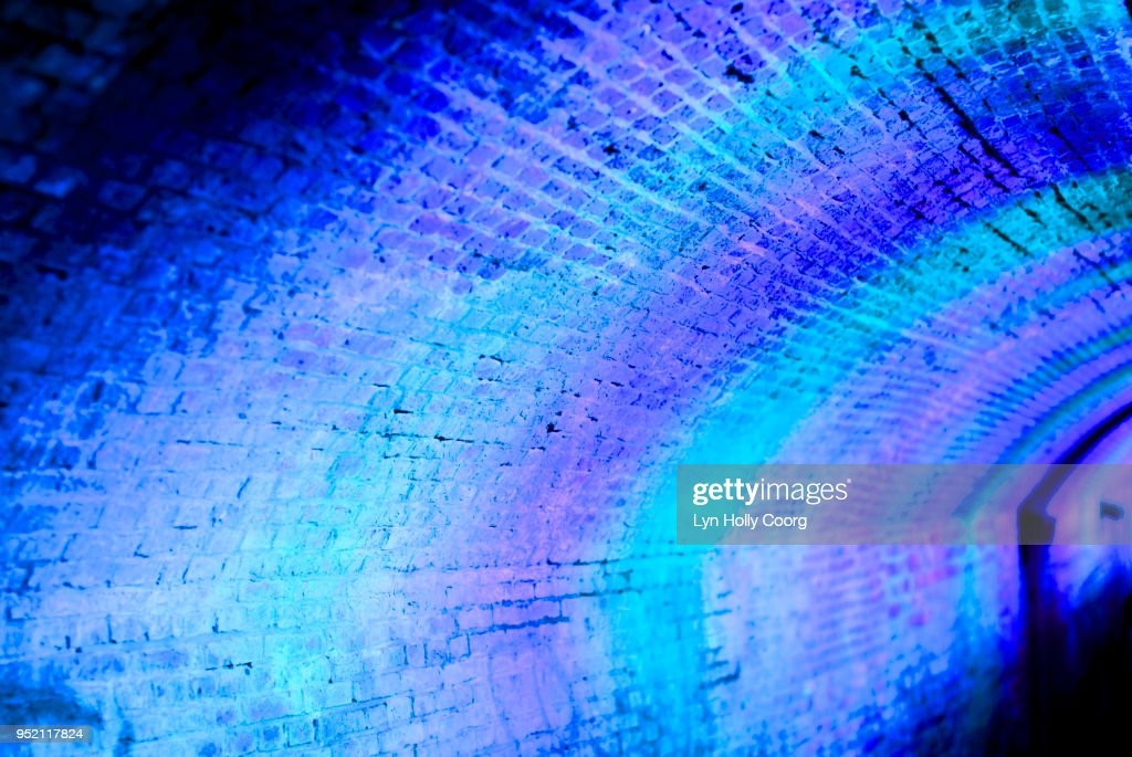 Defocussed blue and purple lights at night in tunnel : Stock Photo
