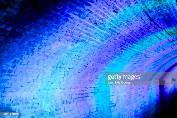 defocussed blue and purple lights at night in tunnel - lyn holly coorg stock photos and pictures