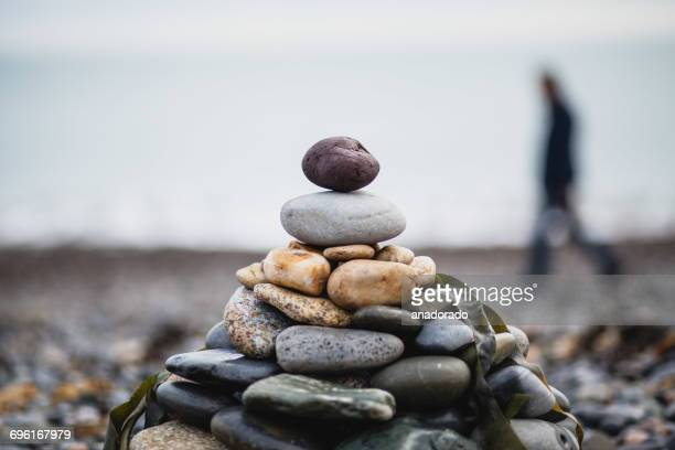 Defocussed person walking past a stack of pebbles on the beach, Ireland