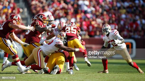 DeForest Buckner and Brock Coyle of the San Francisco 49ers tackle Chris Thompson of the Washington Redskins during the game at FedEx Field on...