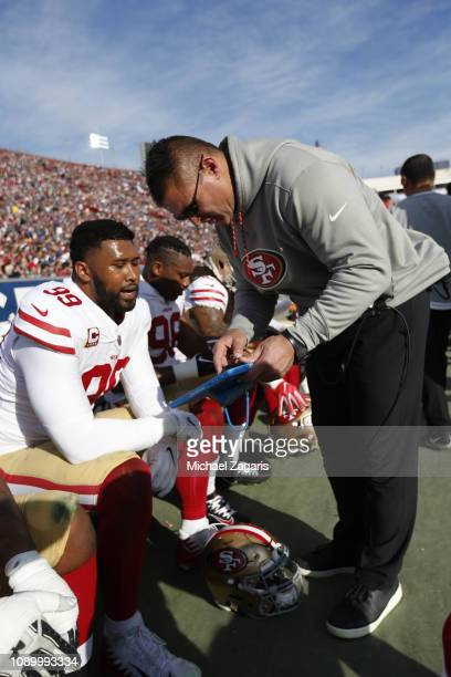 DeForest Buckner and Defensive Line Coach Jeff Zgonina of the San Francisco 49ers talk on the sideline during the game against the Los Angeles Rams...
