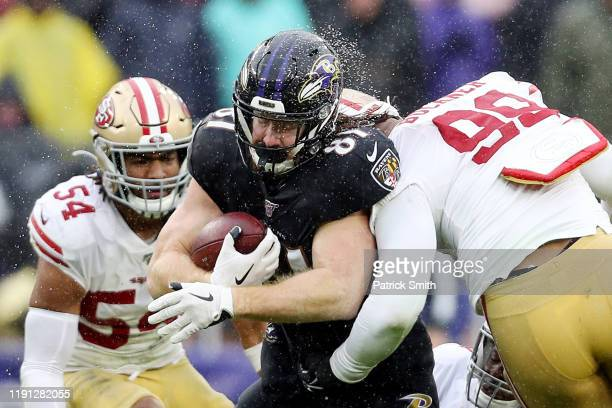 DeForest Buckner of the San Francisco 49ers hits Hayden Hurst of the Baltimore Ravens during the first half at MT Bank Stadium on December 01 2019 in...