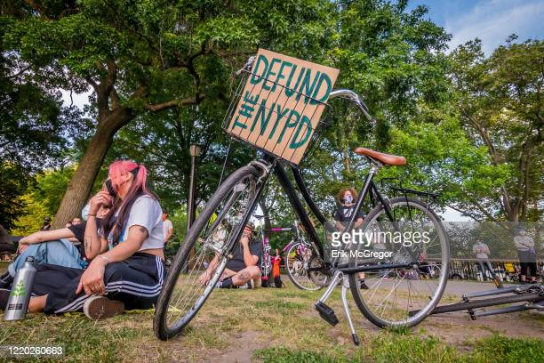 Defund The NYPD sign on a bicycle Greenpoint residents gathered at McCarren Park for a socially distancing rally and vigil demanding justice for all...