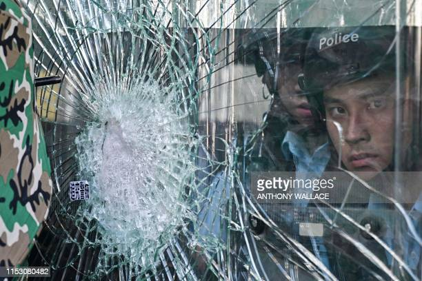 TOPSHOT degaPolice standing inside the government headquarters look at protesters who tried to smash their way into the building in Hong Kong on July...